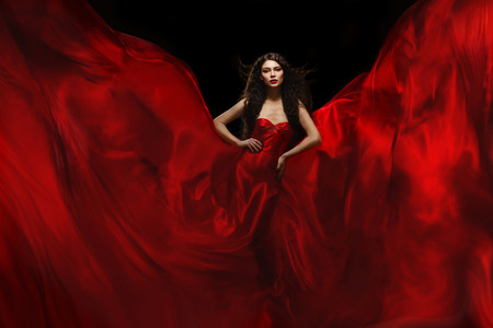 satin dress: Gorgeous woman standing in red flying atlas flames over black background