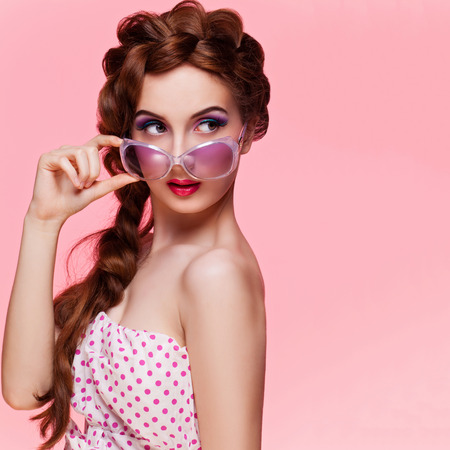 Stylish retro style beautiful woman wearing polka dot dresss and sunglasses. Over pink background Stock Photo - 38687133
