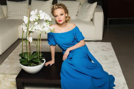 guest room: Bella moda giovane donna che indossa abito lungo blu, seduta su tavolino in camera per gli ospiti Archivio Fotografico