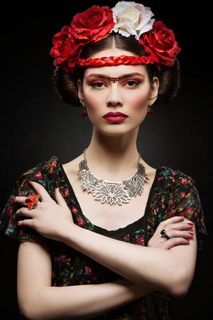 labios rojos: Mujer joven hermosa con un rojo brillante hacer mirar como Frida Kahlo. Sobre fondo negro Foto de archivo