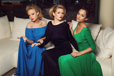evening gowns: Three beautiful young women in evening gowns sitting on creamy sofa Stock Photo