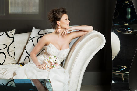 Beautiful young woman in wedding gown sitting on white sofa in interior Standard-Bild