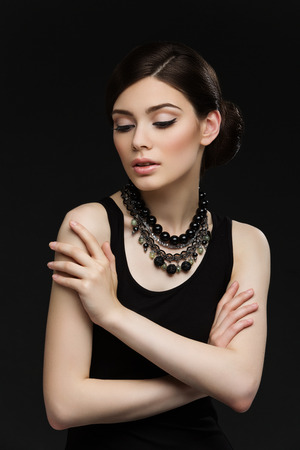 Portrait of gorgeous young woman with necklace over black background