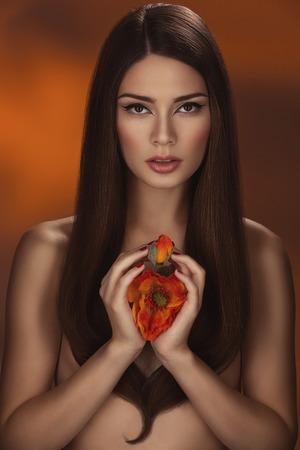 Beautiful young woman holding poppy over orange background Stock Photo