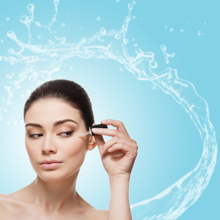 Bella giovane donna applicare il siero idratante anti-età per il contorno occhi sotto. Isolato su sfondo azzurro con spruzzi d'acqua. Piazza composizione. Copia spazio.