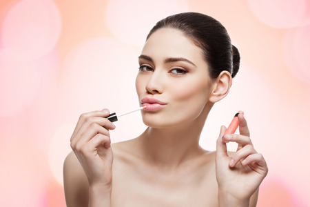 Beautiful young woman applying coral color lipgloss on lips. Isolated over white background, Copy space. photo