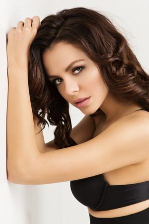 sexy woman standing: Closeup portrait of beautiful young sexy woman standing across white wall wearing blck bra Stock Photo