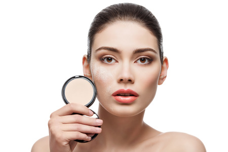 skintone: Beautiful young woman holding conrainer with pressed powder next to her face. Isolated over white background. Stock Photo