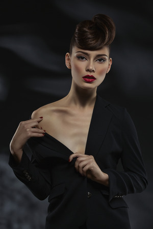 Beautiful young woman wearing black jacket showing her shoulder over black background
