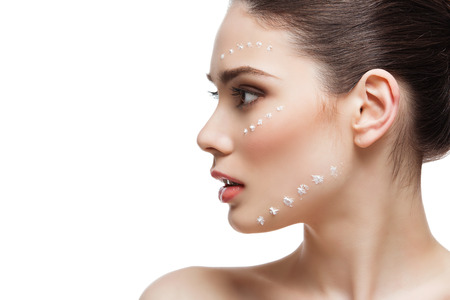 moisturize: Close up of beautiful young woman profile with cream dots on face. Isolated. Copy space