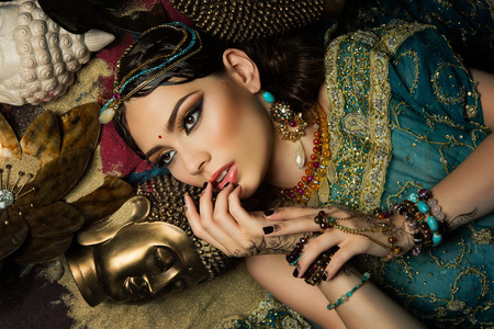 gorgeous girl: Portrait of gorgeous young woman lying in sand with buddha heads