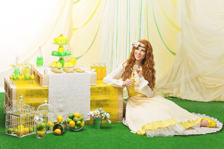 Beautiful young bride in yellow dress siiting near party table with flowers and wedding cake photo