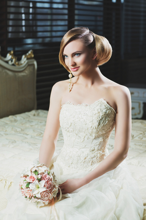 fancy dress: Beautiful young bride with makeup and fancy hairstyle in fancy dress sitting on bed
