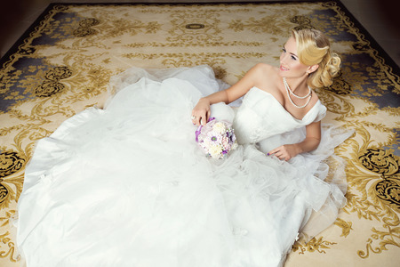 wedding dress: Beautiful young bride in white fluffy dress lying on carpet Stock Photo