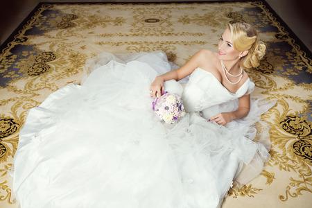 matrimonio feliz: Novia joven hermosa en vestido de blanco esponjoso mentir sobre la alfombra