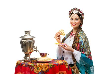 Beautiful young woman in traditional Russian costume sitting in front of table with pancake in her hand. Isolated