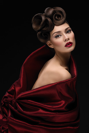 Beautiful young woman with fashionable hairstyle and makeup in red textile looking like tulip