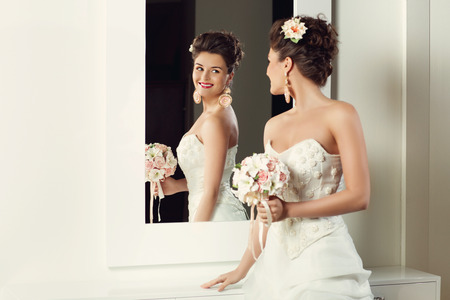 mirror: Beautiful young bride in stylish wedding gown standing near mirror
