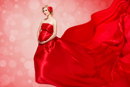 Beautiful elegant pregnant young woman standing wearing flying red fabric with rose in hair. Isolated over red background.