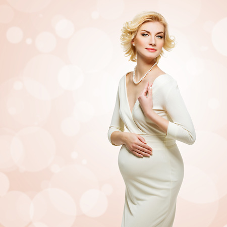 pregnant blonde: Beautiful elegant pregnant young woman wearing white long dress standing over coral background with bokeh. Copy space. Isolated. Stock Photo