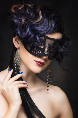 Closeup portrait of beautiful young woman with curly blue hair wearing masquerade mask over black background