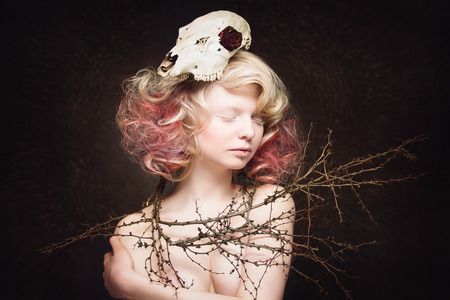 red animal: Portrait of beautiful young woman with animal scull on head and branches around her shoulders over dark background