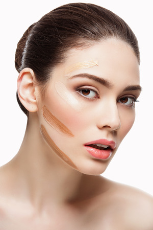 Closeup portrait of beautiful young woman with four shades of liquid foundation on face. Isolated over white background. Stock Photo