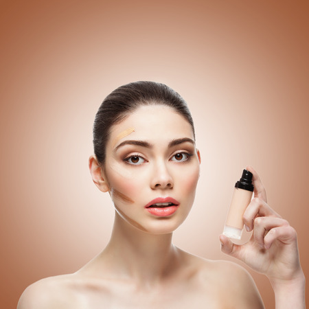 foundations: Close-up of beautiful young woman with four shades of liquid foundation on face and bottle in hand. Isolated over brown background. Copy space. Square composition.