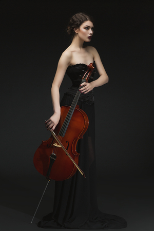 instrumentalist: Beautiful young woman standing in black long skirt and corset with cello. Over black background.