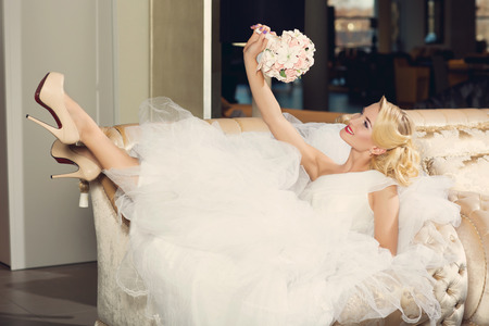 Beautiful young woman dressed as bride in fancy wedding gown lying on sofa looking at bouquet. Interior shoot. Standard-Bild