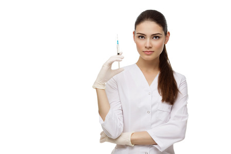 Beautiful young doctor woman in medical robe holding syringe. Isolated over white background. Copy space. Stock Photo