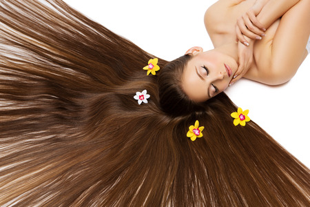 Beautiful young woman with very long natural hair and flowers on it lying on back. Isolated over white background. Stock Photo