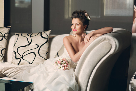 Beautiful young bride in fashionable gown with sitting on sofa. Interior photo.