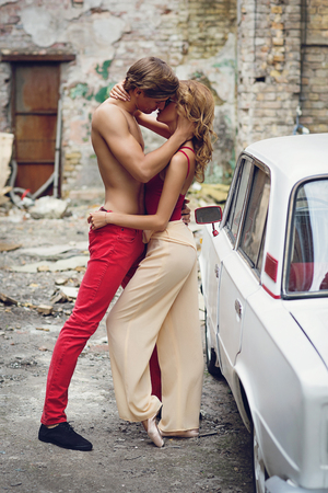 women kissing women: Beautiful young couple standing near old car kissing each other. Outdoor shot with damaged building on background.
