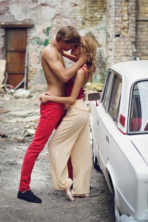 personas besandose: Pareja joven hermosa que se coloca cerca del coche viejo bes�ndose. Tiro al aire libre con el edificio da�ado en el fondo.