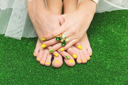 minx: Closeup of woman toes and fingers with yellow, green nail polish.