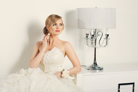 Beautiful young bride in wedding gown sitting near design lamp. Interior shot. Stock Photo