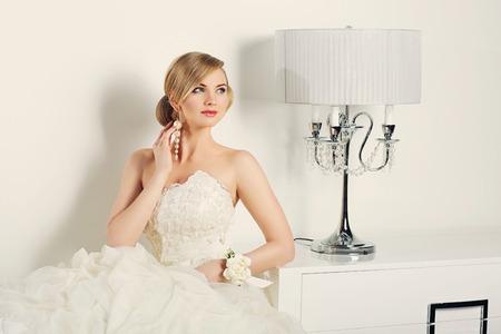 interior shot: Beautiful young bride in wedding gown sitting near design lamp. Interior shot. Stock Photo