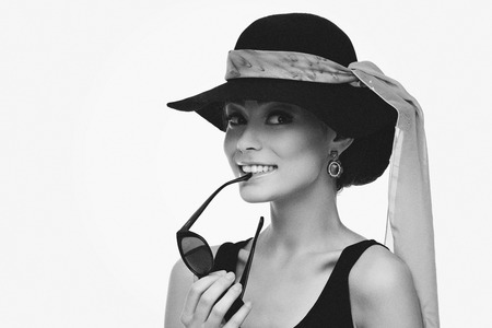 Beautiful young woman in retro style wearing hat with scarf and holding sunglasses Banque d'images