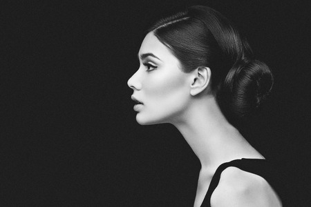 Closeup shot of beautiful young woman profile over black background Stock Photo