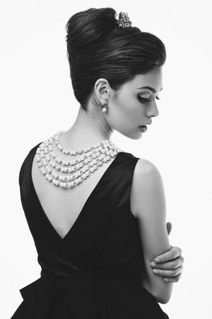Gorgeous young woman looking like Audrey Hepburn in Breakfast at Tiffany's movie. Isolated over white background Stock Photo - 43550153