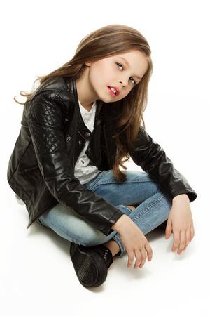 bata blanca: Ni�a en la chaqueta leathet moda y pantalones vaqueros sentados en el suelo. Aislado sobre fondo blanco.