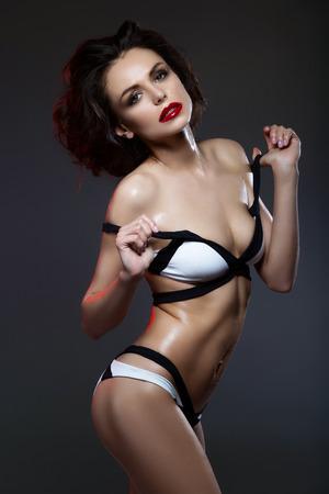wet lips: Beautiful slim young woman with red lips and wet skin in black and white bikini over dark background. Studio shot. Stock Photo