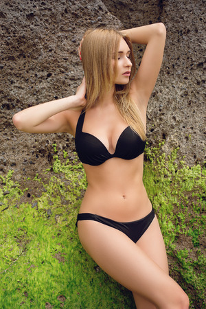 hait: Beautiful young woman with long blond hait in black bikini standing near cliff. Outdoor shot. Tenerife.