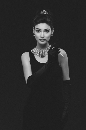 Beautiful woman looking like Audrey Hepburn standing with cigarette-holder