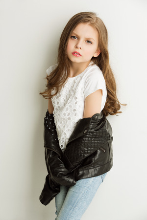leather coat: Little girl in fashion leathet jacket and jeans standing near white wall.Studio shot. Stock Photo