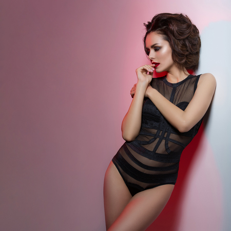 Beautiful young woman with bright makeup and red lips wearing black sexy bodysuit standing near wall. Over pink background. Copy space, Square composition. Zdjęcie Seryjne