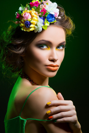 Beautiful young woman with bright colorful makeup and flowers in hair. Over dark green background.