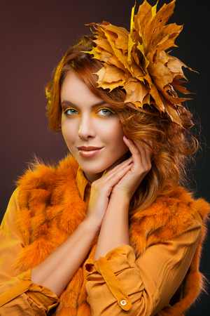 fall of the leaves: Beautiful young woman in orange, yellow make-up and clothes with autumn leaves in her red curly hair