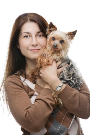amigos abrazandose: Retrato de una mujer que sostiene un lindo yorkshire terrier aislados sobre fondo blanco. Foto de archivo